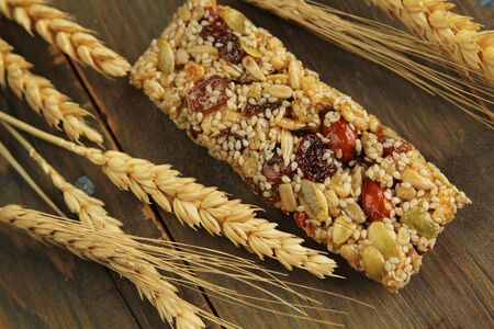 Granola bar with nuts and dry wheat on a wooden table Stock Photo - 14814170