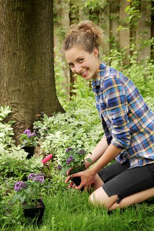 smiling teen gardening purple flowers in a nice garden photo