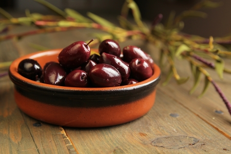 Kalamata olives into in a bowl on wooden table