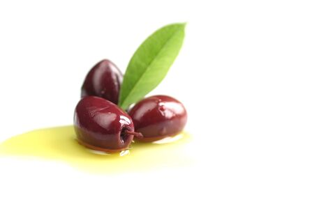 Kalamata olives into with leaf on white background photo