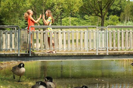 sweet sixteen: Teenager girl playing with hands on a bridge by a nice summer day