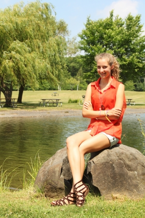 Teenager girl with a orange top sit on a rock in a park