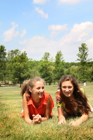 Two teenagers laying doen in a grass photo