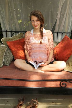Happy teen reading a book outside in a couch photo