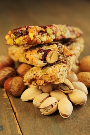 Three granola bar with nuts and dry fruits on a wooden table