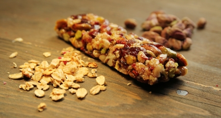 Granola bar with nuts, dry fruits and musly on a wooden table