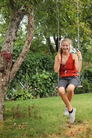 Girl sit on a swing outside in a garden photo