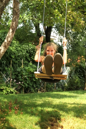 Girl sit on a swing and swinging outside in a garden photo