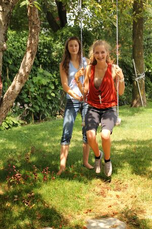Girl on a swing with a best friend outside in a garden photo