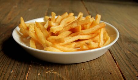 French fries with salt in a plate on a wooden table Reklamní fotografie