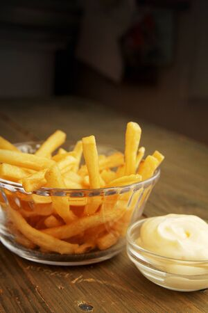 French fries with salt and mayonnaise in a clear bowl