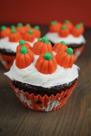 Halloween cupcakes with vanilla icing and creamy pumpkins on top photo