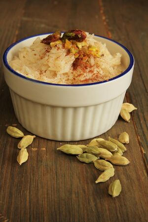 Rice pudding with cardamom on a wooden table