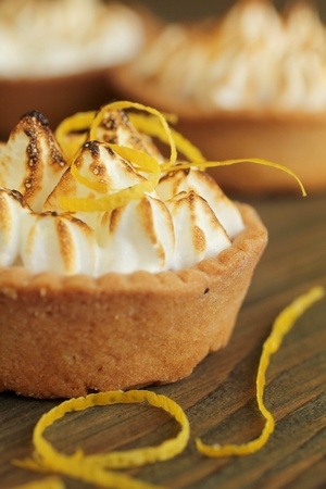 Meringue: Close up of a lemon tart with lemon zest on a wooden table