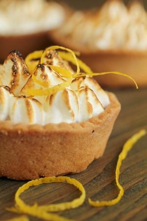 pie de limon: Primer plano de una tarta de lim�n con c�scara de lim�n en una mesa de madera Foto de archivo