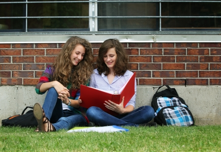 Two smiling girls sit on a grass with their bag, books and study their lessons photo