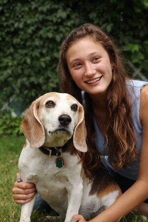 Smiling teenager with her old beagle dog photo