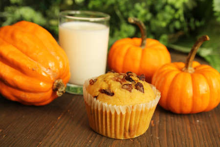Pumpkin muffin with a glass of milk and pumpkin on a wooden table photo