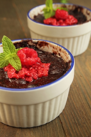 Chocolate pudding with fresh raspberry and mint on a wooden table