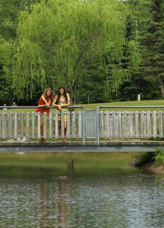 Two best friends on a wood bridge looking at the ducks photo