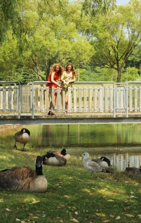 Two teenagers on a bridge looking for duck in water photo