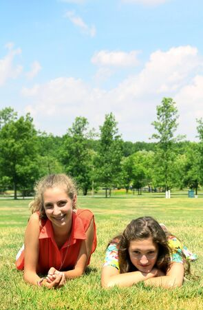 Two beautiful teenagers laying down in grass and looking at the camera Stock Photo