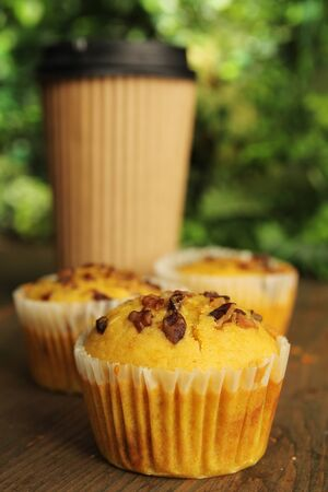 Carrot muffin with nuts and a coffee to go in the background photo