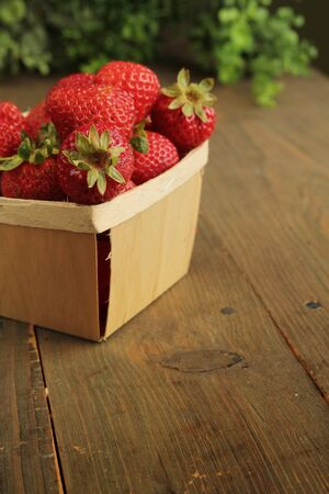 Basket full of strawberries on a wooden table