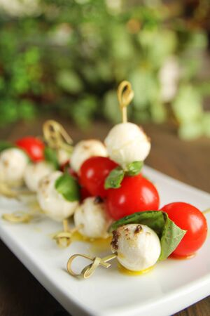 Delicious bocconcini, tomato and basil on toothpick