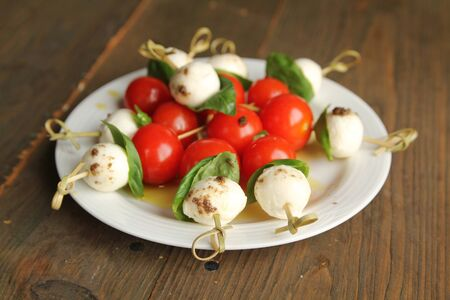 Bocconcini, tomato and basil on toothpicks in a white plate    Stock Photo
