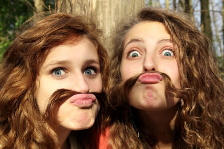 Two best friends doing mustaches with their hairs