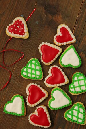 Variety of green and red heart shape cookies on a wooden table photo