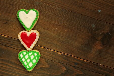 Three green and red heart shape cookies on a wooden table photo