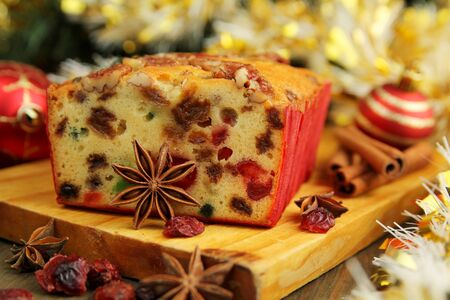 Traditionnal fruit cake for christmas with anise, cinamon and dried cranderries with christmas background