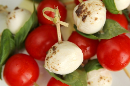 Close up of delicious skewer with bocconcini, cherry tomatoes and basil or caprese