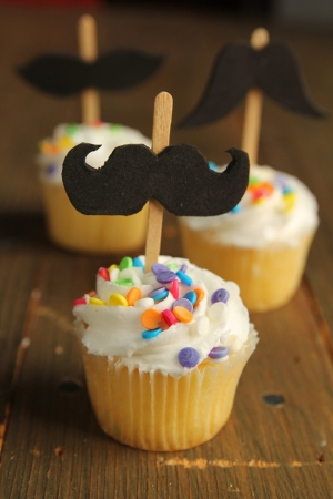 Cupcakes with black moustaches and colorful sprinkles Stock Photo