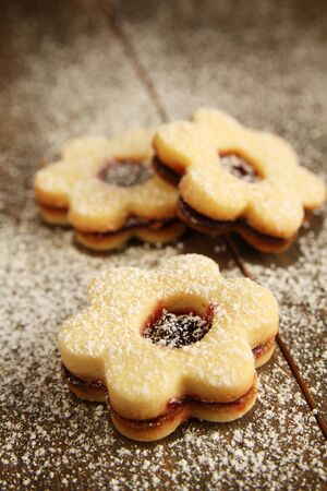 Flowers shape cookies cover with powder sugar on a wooden table photo