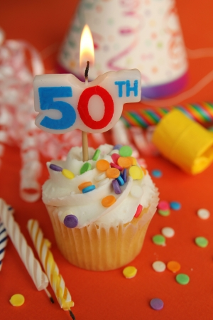 Delicious cupcake with 50th candle on top with hat, candle and noisemaker in background photo