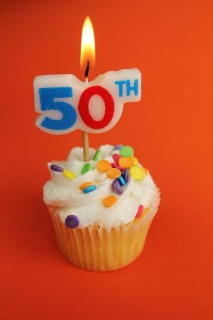 decoracion de pasteles: Delicioso cupcake con vela n�mero 50 en la parte superior sobre fondo naranja Foto de archivo
