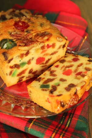 Slice of a traditionnal fruit cake for christmas on a red and green tablecloth photo