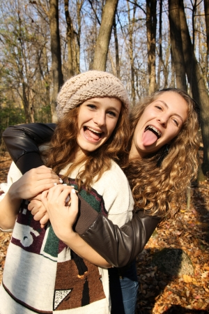 Two girls best friends having fun in a forest during autumn photo