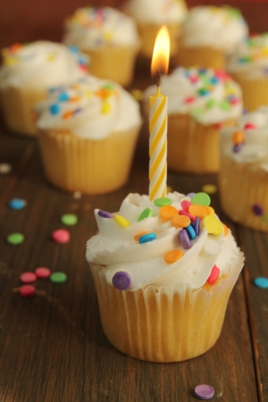 Cupcakes with colorful sprinkles and a yellow candle on top with cupcakes in background photo