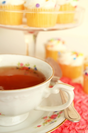 Delicious tea in a nice cup with little cakes Stock Photo - 16681981