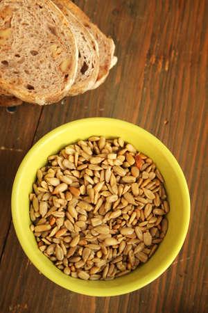 sunflower seeds: Sunflower seeds in a green bowl and nuts bread on a wooden table Stock Photo