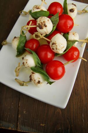 Bocconcini, tomato and basil on toothpicks in a white plate    Imagens