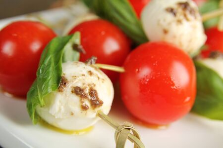 appetiser: Close up of a bocconcini with basil and cherry tomatoes on skewer for appetiser