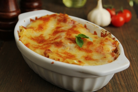 Fresh lasagna in a white container with basil photo