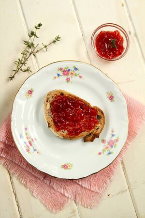 Top view of a a sliced of nuts bread toast with strawberry jam and a little container with extra jam on white wooden background photo