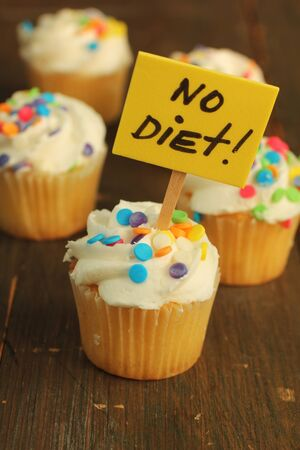 Cupcakes with colorful sprinkles and no diet sign photo