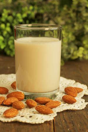 Glass of almond milk with almond on a wooden table